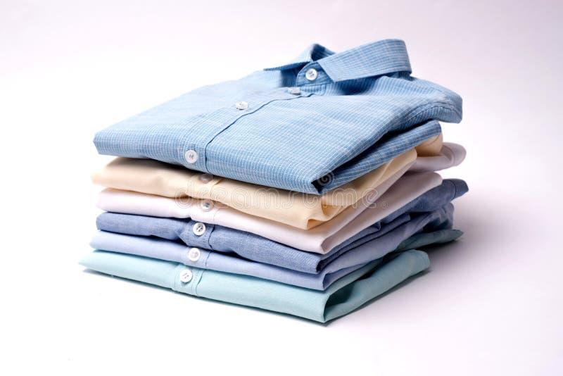 Camisas clássicas do ` s dos homens empilhadas no fundo branco foto de stock