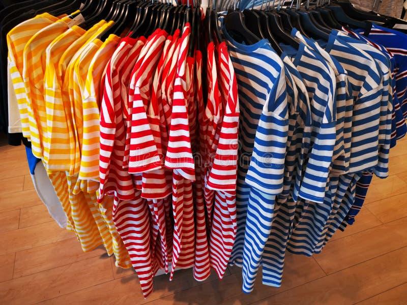 Camisas coloridas do verão nos ganchos imagens de stock royalty free