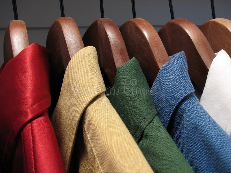 Camisas coloridas em ganchos de madeira imagens de stock royalty free