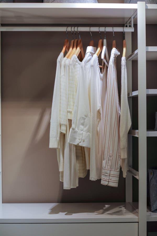 Camisas coloridas luz que penduram no armário imagem de stock royalty free