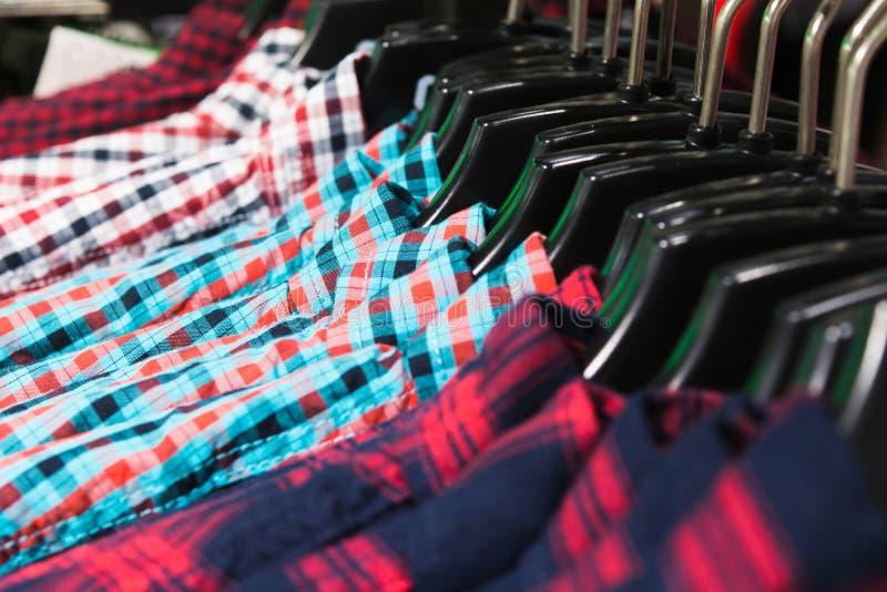 Camisas coloridas no gancho em uma loja imagem de stock