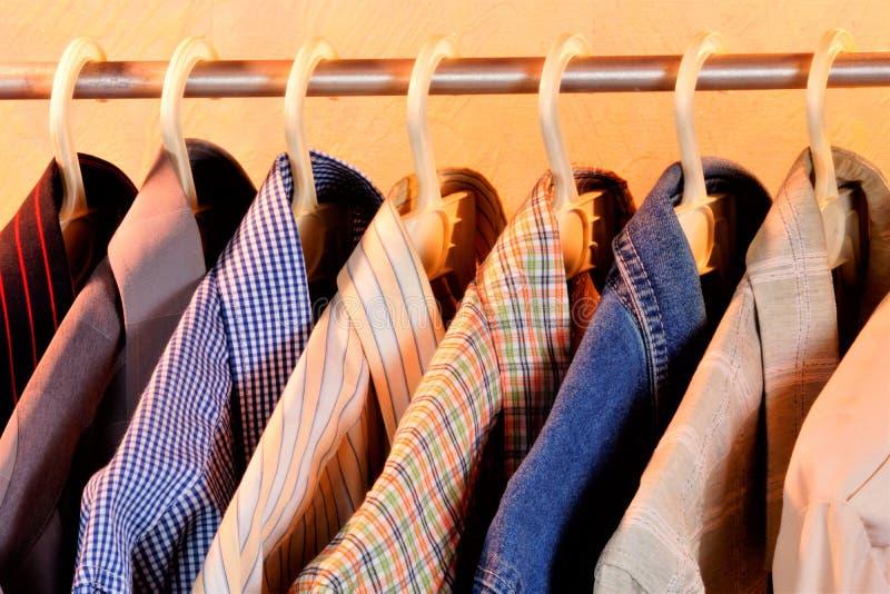 Camisas coloridas no gancho, no tipo de homens e na roupa das mulheres, roupa interior fotografia de stock royalty free