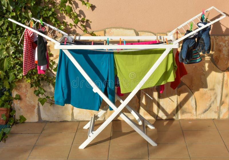camisas coloridas, peúgas, pijamas, t-shirt, cuecas, luvas e a outra roupa molhados após o lavagem, realizar em uma linha de lava imagem de stock royalty free