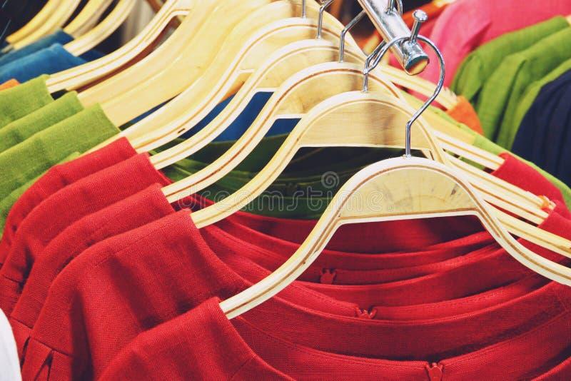 Camisas coloridas que penduram no fim da cremalheira acima imagem de stock royalty free