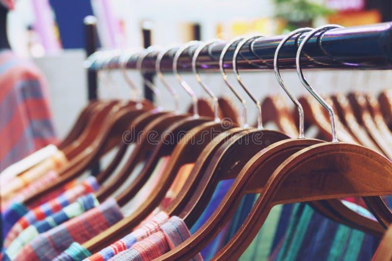 Camisas coloridas que penduram no fim da cremalheira acima foto de stock