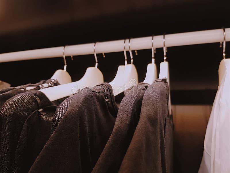 Camisas da roupa ocasional que penduram dentro do vestuário com foco seletivo fotos de stock