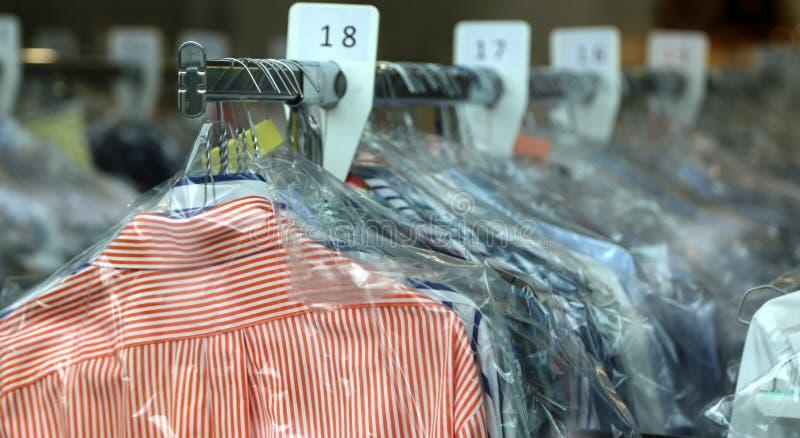 Camisas da tinturaria em ganchos na limpeza química imagem de stock royalty free