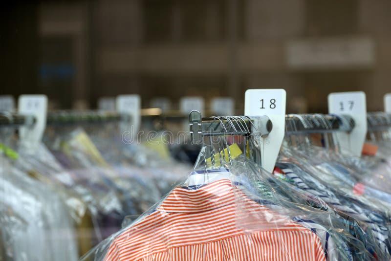 Camisas da tinturaria em ganchos na limpeza química imagens de stock