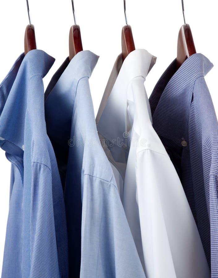 Camisas de alineada azules en perchas de madera foto de archivo