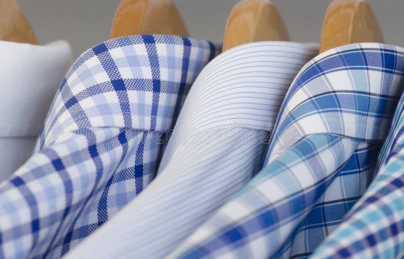 Camisas de vestido azuis sortidos em ganchos de madeira imagens de stock royalty free