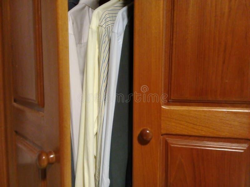Camisas de vestido no armário de madeira com boa luz imagem de stock