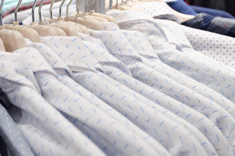 Camisas del ` s de los hombres hechas del color blanco de la luz del algodón en la suspensión de capa en la tienda fotografía de archivo libre de regalías