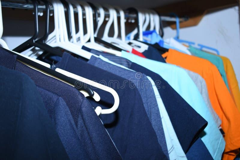 Camisas dentro de um vestuário pendurado em uma cremalheira imagens de stock royalty free