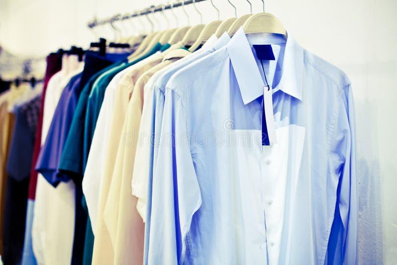Camisas do homem com a etiqueta em ganchos fotos de stock