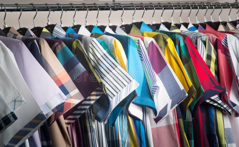 camisas do homem em ganchos imagens de stock