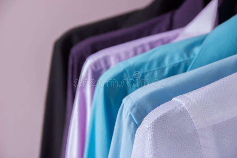 Camisas do ` s dos homens coloridos que penduram em ganchos foto de stock