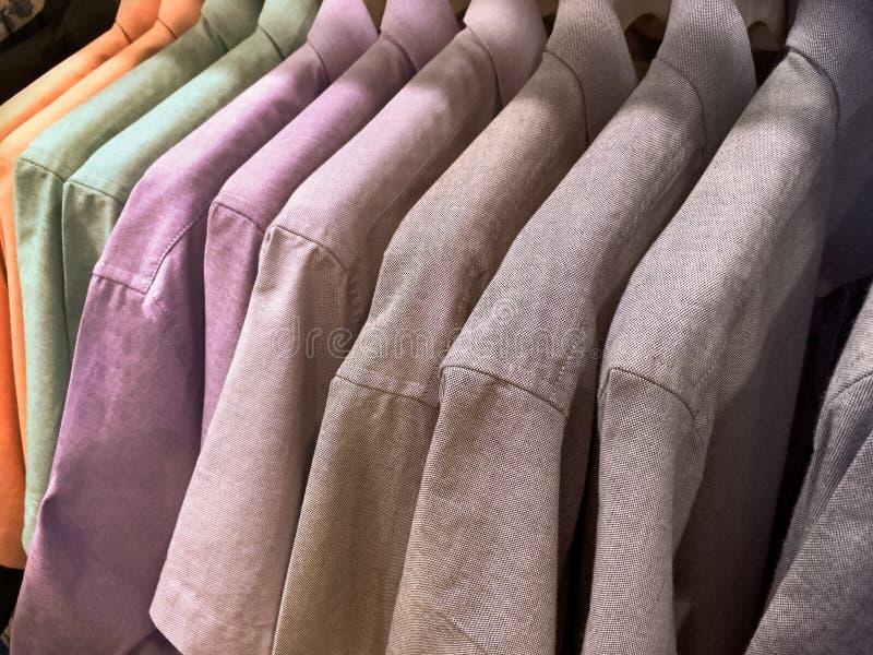 Camisas do ` s dos homens que penduram na cremalheira fotos de stock