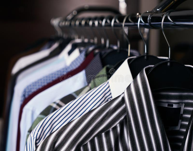Camisas dos homens em cores diferentes em ganchos imagens de stock