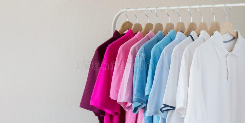 Camisas dos homens que penduram na fileira na cremalheira imagens de stock royalty free