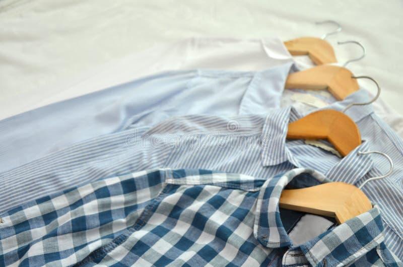 4 camisas en las sillas de madera colocadas en la cama en sombras del blanco, imagen de archivo