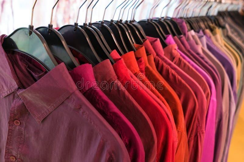 Camisas masculinas dos homens em ganchos em um trilho do armário do vestuário da loja fotografia de stock
