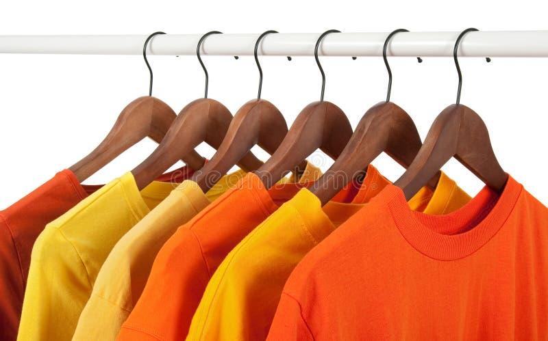 Camisas ocasionais amarelas e alaranjadas em ganchos foto de stock royalty free