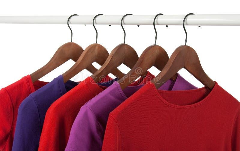 Camisas ocasionais vermelhas e roxas em ganchos fotos de stock royalty free