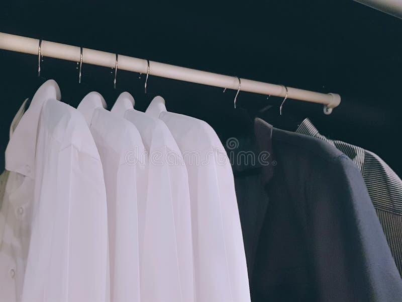 Camisas para os homens que penduram dentro do vestuário fotografia de stock