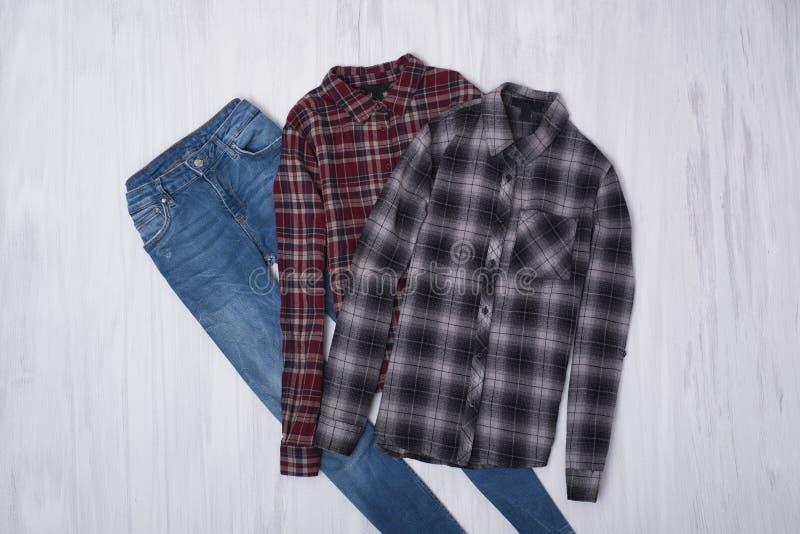 Camisas quadriculados e jeaens no fundo de madeira Co elegante fotos de stock royalty free