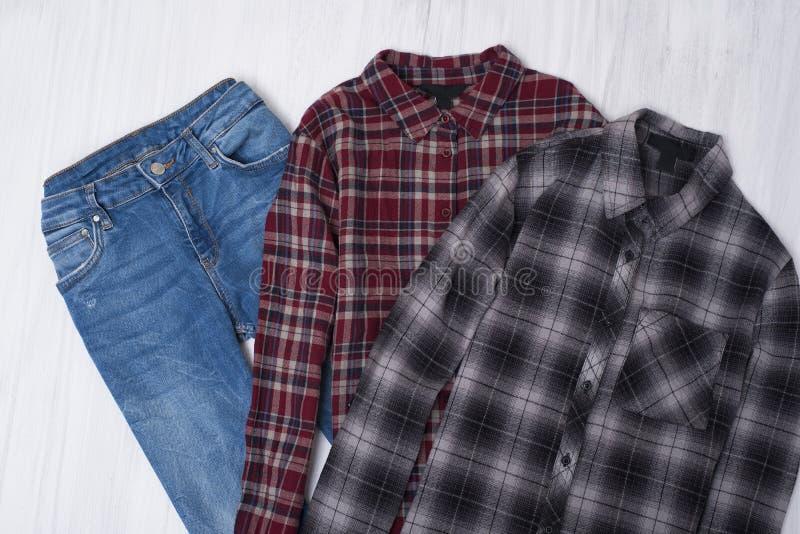 Camisas quadriculados e jeaens no fundo de madeira Co elegante fotos de stock