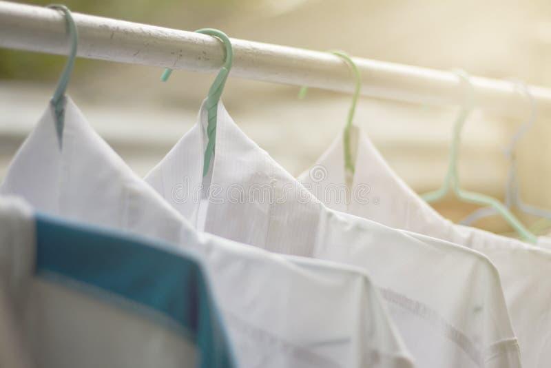 Camisas que penduram sobre no trilho ou na roupa aberta fora no dia da lavanderia imagem de stock