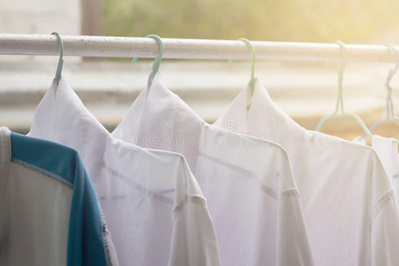 Camisas que penduram sobre no trilho ou na roupa aberta fora no dia da lavanderia foto de stock royalty free
