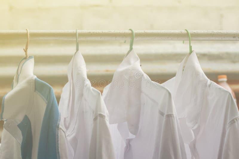 Camisas que penduram sobre no trilho ou na roupa aberta fora no dia da lavanderia fotos de stock