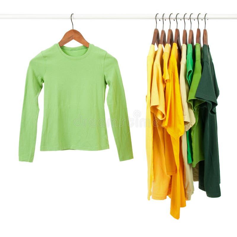 Camisas verdes e amarelas em ganchos de madeira imagem de stock royalty free