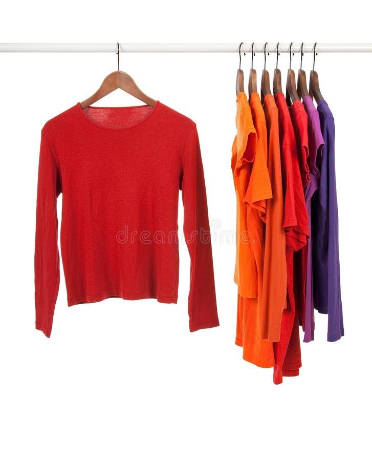 Camisas vermelhas e roxas em ganchos de madeira imagens de stock royalty free