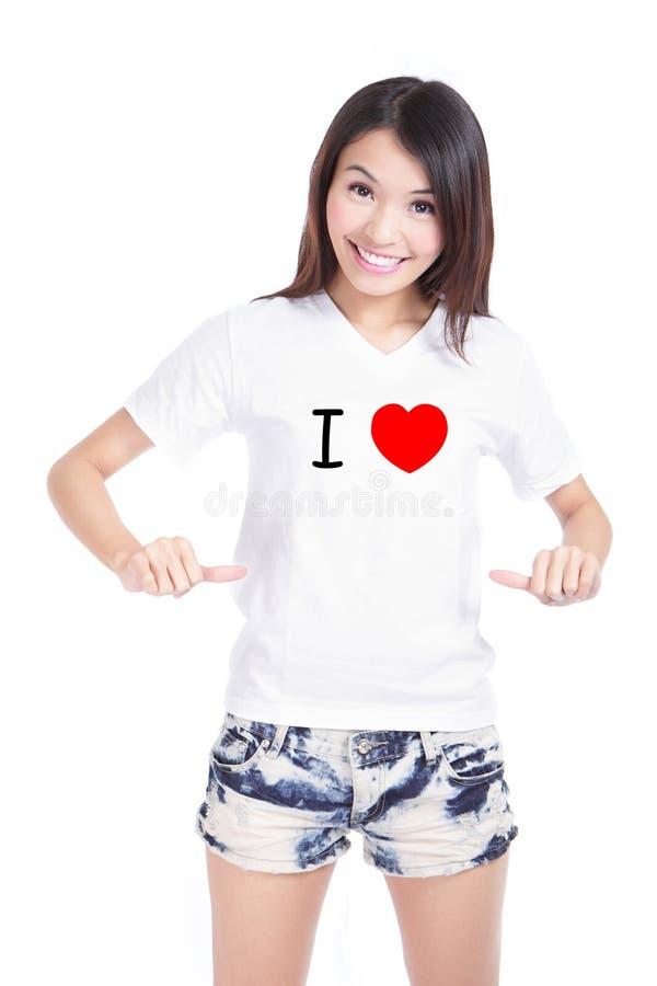 Camiseta blanca de la demostración feliz de la muchacha con el texto (amor de I) imagen de archivo libre de regalías