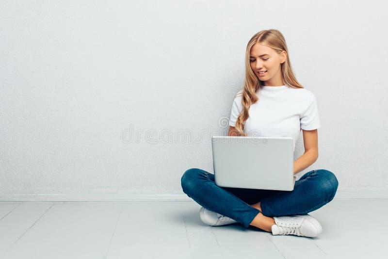 Camiseta blanca que lleva de la mujer feliz que se sienta en el piso con el ordenador portátil en fondo gris fotografía de archivo