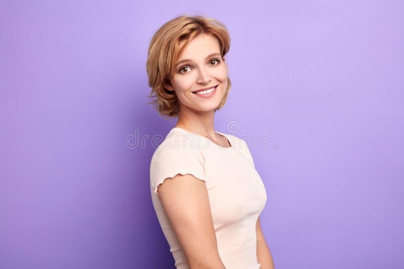 Camiseta blanca que lleva de la mujer rubia hermosa sobre fondo azul aislado imágenes de archivo libres de regalías