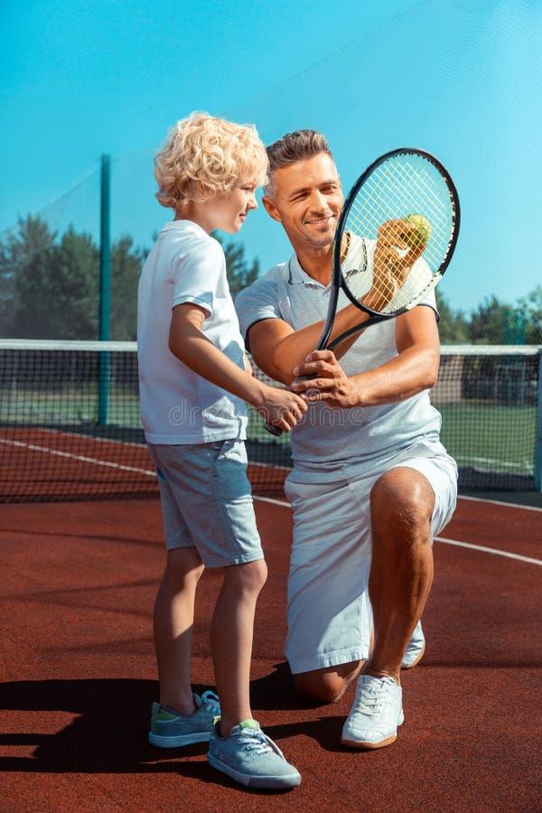Camiseta blanca que lleva del muchacho rubio-cabelludo rizado que mira la pelota de tenis imágenes de archivo libres de regalías