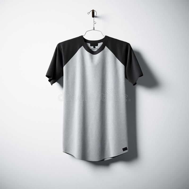 Camiseta de algodón en blanco de los colores grises y negros que cuelgan en el centro el muro de cemento vacío Maqueta clara de l fotografía de archivo