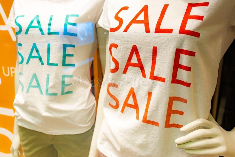 Camiseta del lema de la venta de la estación en dos maniquíes en ventana en el color del centro comercial, rojo y verde fotos de archivo libres de regalías