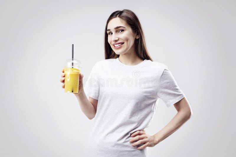Camiseta gris blanca que lleva de la mujer hermosa joven que sonríe con el zumo de naranja a disposición Retrato aislado en el fo foto de archivo