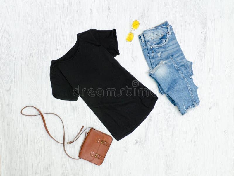 Camiseta negra, vaqueros rasgados, bolso y gafas de sol fashionable imágenes de archivo libres de regalías