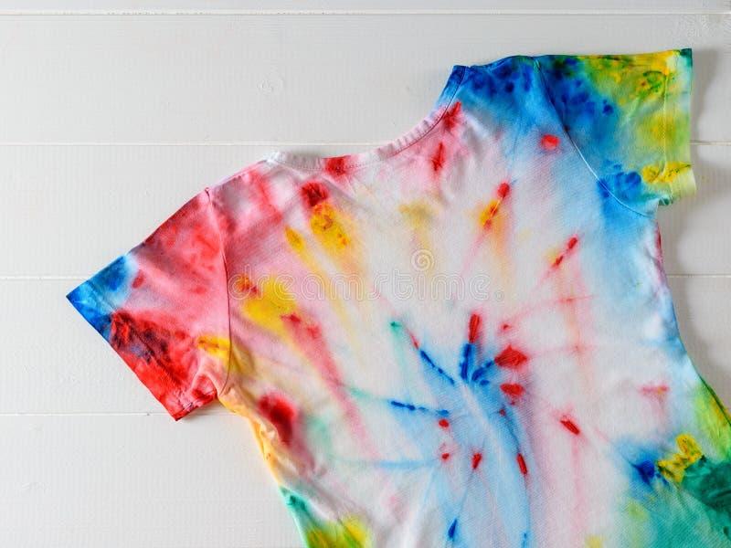 Camiseta pintada en estilo del teñido anudado en una tabla de madera blanca imágenes de archivo libres de regalías