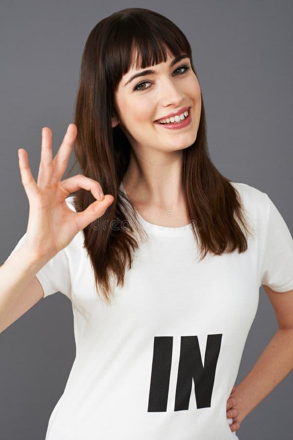 Camiseta que lleva del partidario de la mujer joven impresa con EN lema imágenes de archivo libres de regalías