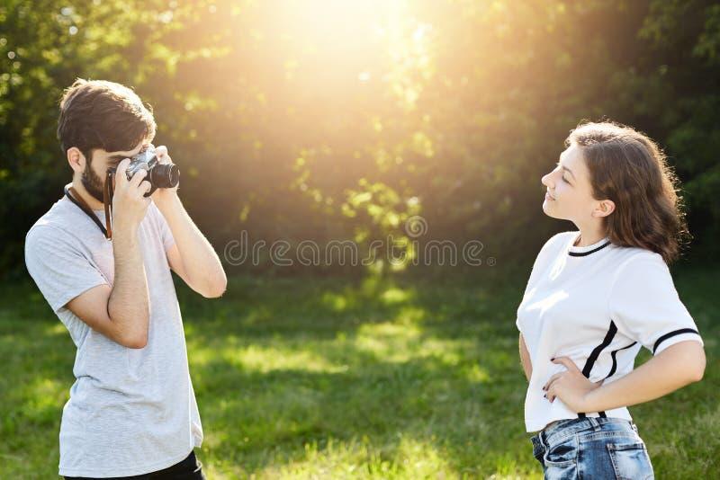 Camiseta que lleva femenina joven y vaqueros que presentan in camera al fotógrafo Varón talentoso joven con la cámara retra que f fotografía de archivo