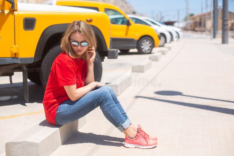 Camiseta que lleva, tejanos y gafas de sol de la mujer hermosa sent?ndose en el ?rea peatonal cerca del coche amarillo fotografía de archivo