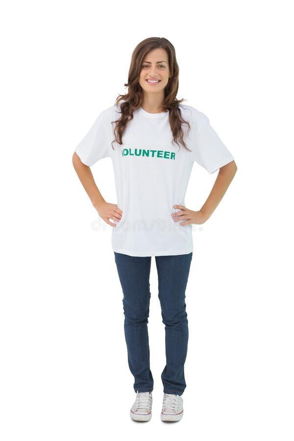 Camiseta voluntaria que lleva de la mujer que pone sus manos en caderas fotos de archivo libres de regalías