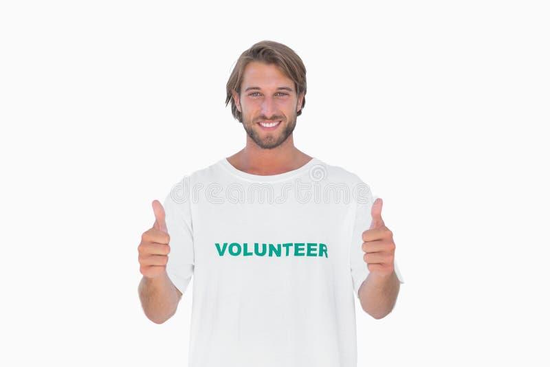 Camiseta voluntaria que lleva del hombre feliz que da los pulgares para arriba fotografía de archivo
