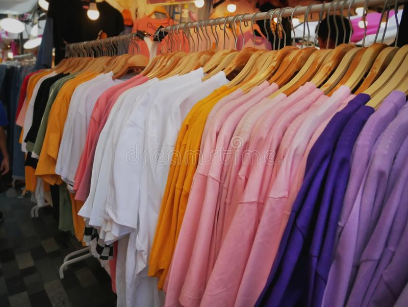 Camisetas coloridas que cuelgan en el estante en la tienda al por menor fotografía de archivo
